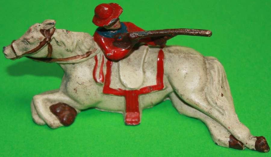 A SCARCE GOOD EXAMPLE OF THE JOHN HILL & CO COWBOY FIRING OVER HORSE
