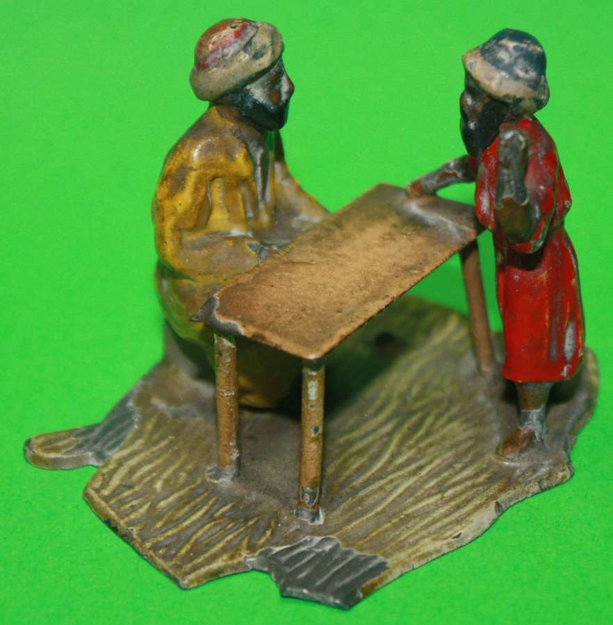 A PAIR OF LEAD ARABS RANTING AT A TABLE