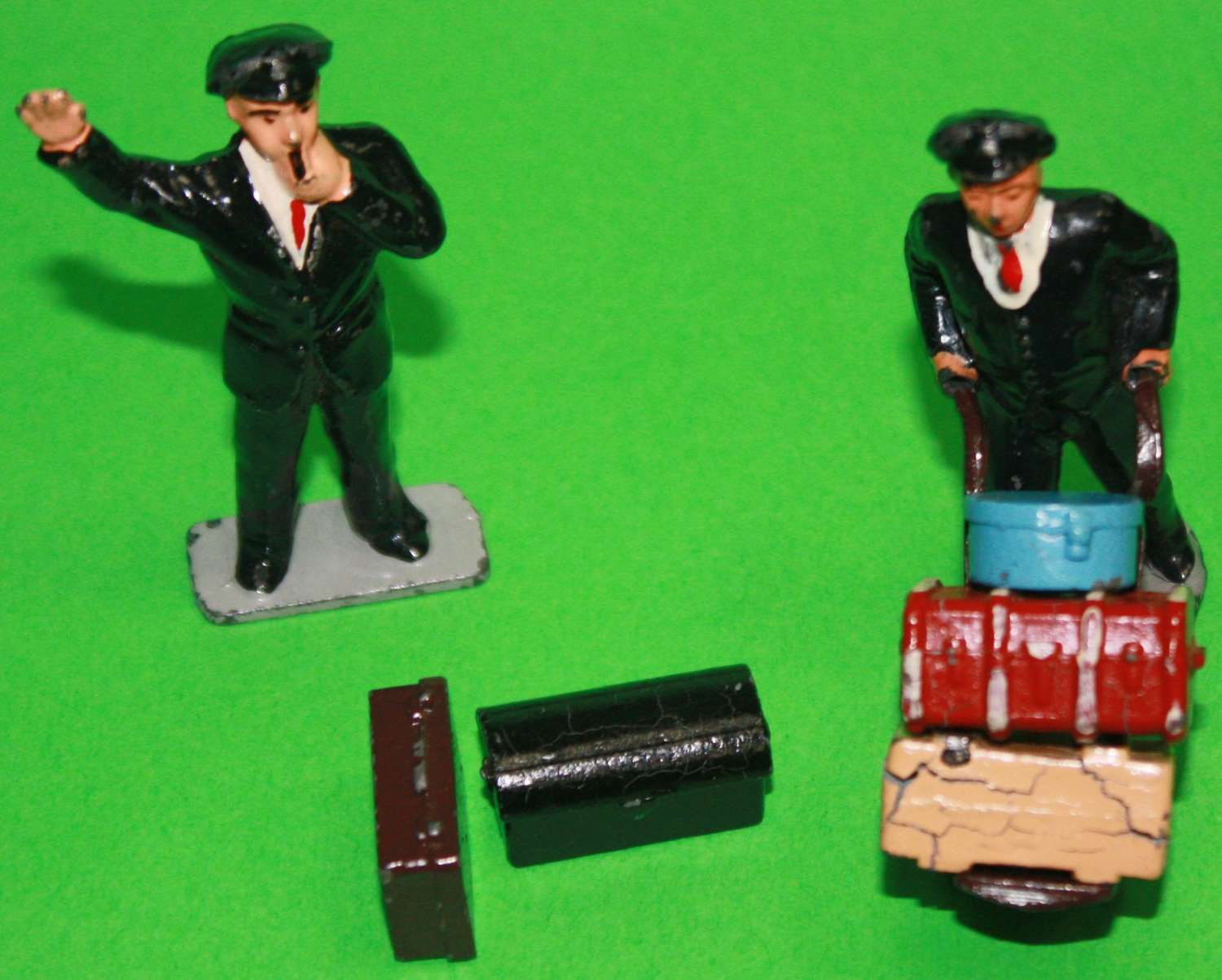 A PAIR OF CRESCENT MADE STATION PORTER AND BITS WITH A RAILWAY GUARD